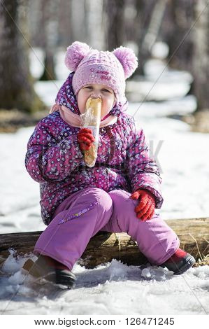 Girl sitting in the winter woods on a log or eating a long loaf of white bread