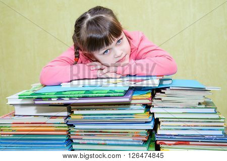 Beautiful girl in a pink jacket hid behind a stack of book