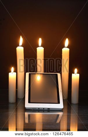 Blackout concept. Lighting candles around tablet like a sanctuary