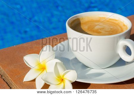 white cup of coffee on the edge of pool