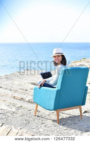 Woman using laptop by the sea, sit in armchair