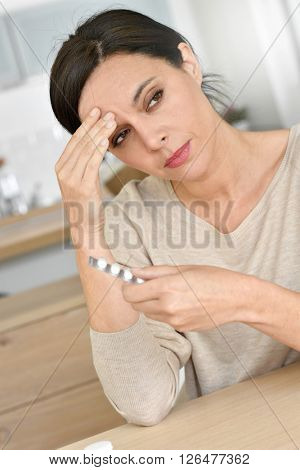 Woman having headache, taking pills