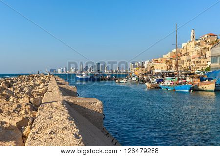 View from breakwater on small port with boats, old Jaffa and Tel Aviv on background under blue sky in Israel.