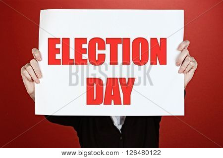 Hands holding card with Election Day text on red background