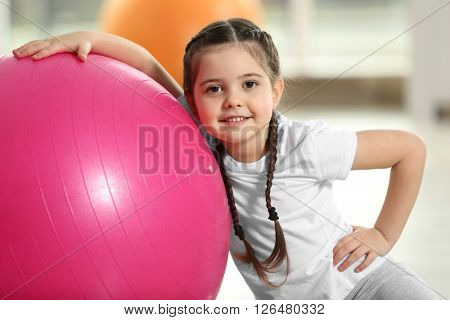 Little cute girl with exercise ball indoor