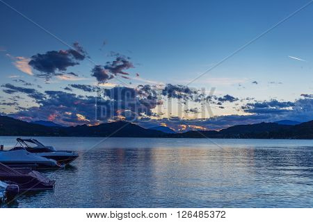Sunset landscape Alpine lake with motor boat, Austria