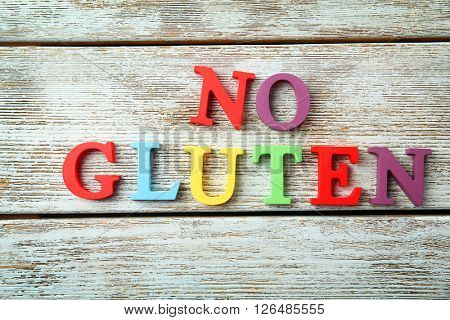 Phrase NO GLUTEN made of colorful letters on wooden background