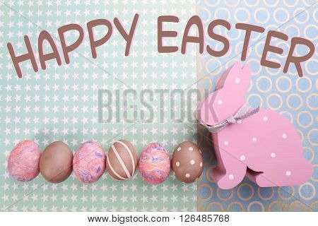 Easter greeting card. Painted eggs with wooden rabbit on paper color background
