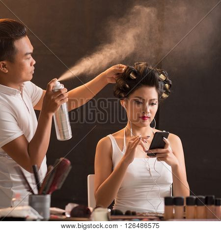 Very attractive Vietnamese woman having her hair done in beauty salon
