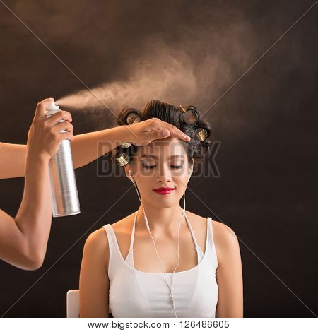 Stylist using hair spay  when working with client