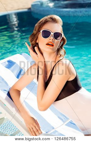 Beautiful brown hair woman near water wearing bikini. Young girl model in sunglasses and elegant black and white sexy swimsuit lingerie near swimming pool with clear blue water. Full relax. Vintage.