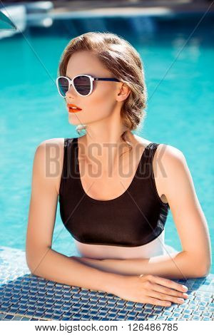 Beautiful brown hair woman in water wearing bikini. Young girl model in sunglasses and elegant black sexy swimsuit lingerie near swimming pool with clear blue water. Relax. Vintage. Closeup portrait.