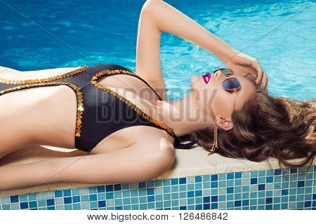 Beautiful brown hair woman near water wearing bikini. Young girl model in sunglasses and elegant black sexy swimsuit lingerie near swimming pool with clear blue water. Full relax. Vintage.