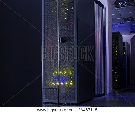 darkened room with rows of modern server hardware in data center