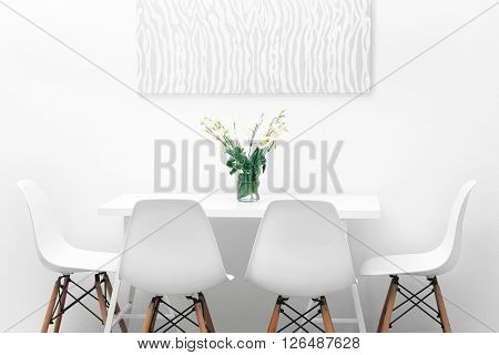 Modern dining room. White chairs and table with bouquet of flowers, abstract picture on the wall