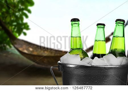 Beer bottles of cold fresh beer in ice bucket, on nature background