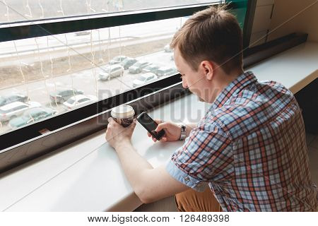 Young man taking a coffee break at cafe touching his smartphone