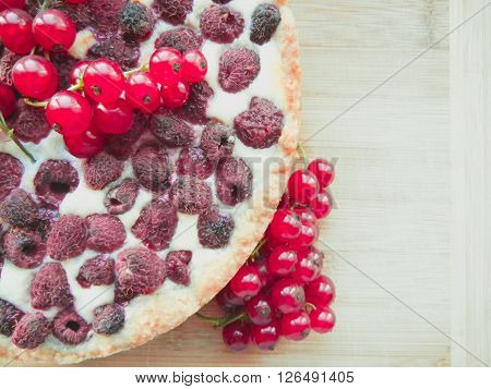 pie with raspberries decorated with red currant berries.
