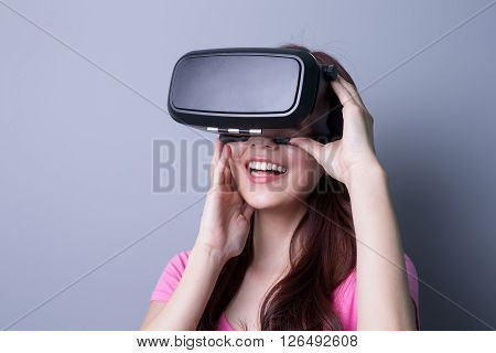 Smile happy woman getting experience using VR-headset glasses of virtual reality at home much gesticulating hands asian beauty