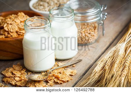 Breakfast Cereal Wheat Flakes, Spikes And Milk Bottles On Wooden Table