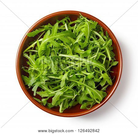 Fresh green arugula in bowl isolated on white background top view