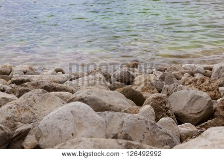 White yellow grey natural boulders with salt levee on blue water edge of Dead Sea with ripples