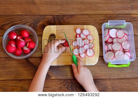 Child cuts vegetables for salad using kitchen knife. Children hands holding a knife and a radish. Vegetables for salad. Top view
