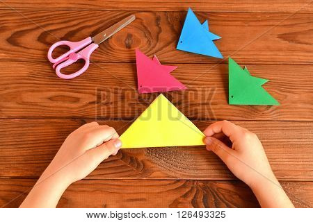 Origami colorful fish, scissors. Child holds paper sheet in his hands and making origami fish. Brown wooden background