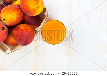 Glass with peach juice and ripe peaches in basket on white wooden surface. Top view