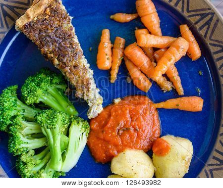 Quiche and vegetables on blue plate