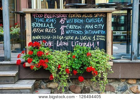 Riga, Latvia - 24-august-2015: Advertising Board And Wooden Box Of Geranium Flowers Near A Restauran