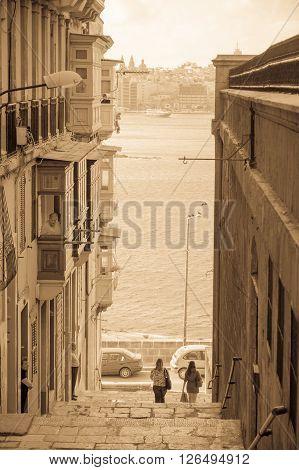 VALLETTA MALTA - APRIL 13 2012: Street scene with view of the port, locals and visitors in Valletta Malta