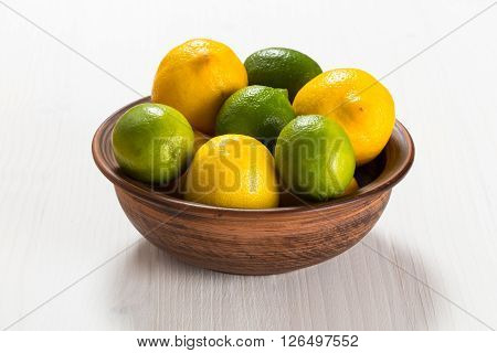 Lemons and limes in a clay bowl - on white wooden table