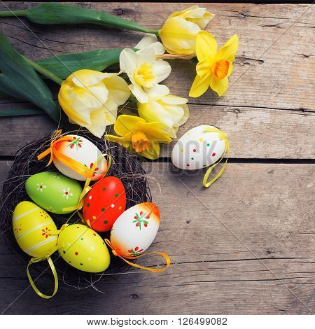 Easter background. Fresh yellow tulips and daffodils flowers decorative eggs in nest on vintage wooden background. Selective focus. Place for text. Square image.