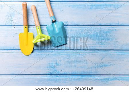 Childhood concept. Garden tools or tools for playing in sand for kids on blue painted wooden planks. Place for text.