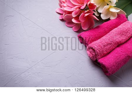 Spa or wellness setting. Set of pink bath towels and tropical flowers on grey textured background. Selective focus. Place for text.
