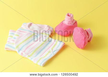 Baby clothing on a yellow background with copy space