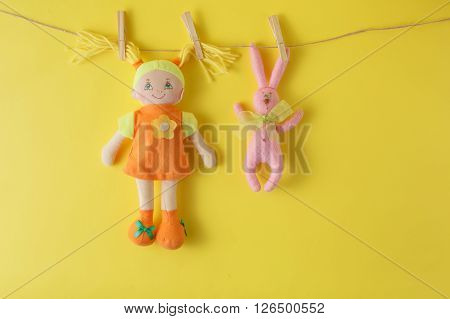 Colorful doll hanging on clothesline on yellow