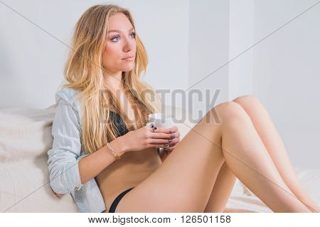 Young woman in lingerie sitting on couch with cup of coffee in the morning, boudoir concept, soft light