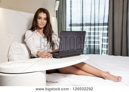 Portrait of a young adult beauty attractive sexy and sensuality happy pretty brunette businesswoman using laptop while lying on bed in hotel room