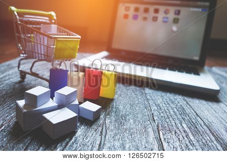 laptop blank screen and hopping cart full of gifts with copyspace online shopping concept.
