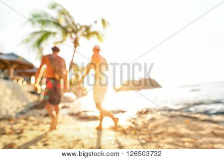 Blurred defocused silhouette of travelers at seaside before sunset - Travel and wanderlust concept with people at Las Cabanas beach by El Nido Palawan - Warm bright filter - Tilted horizon composition