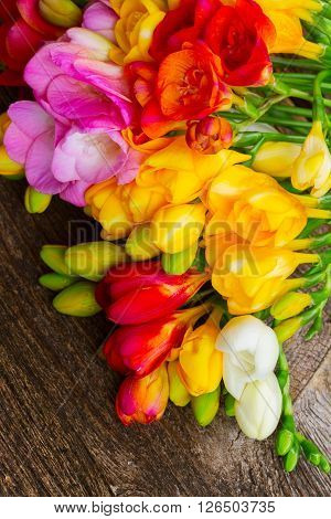 Pile of Fresh freesia flowers  on wooden table