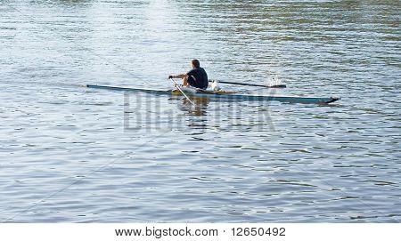 eine einzelne Gezeitenleere / Ruderer / Ruderer auf einem Fluss oder See r. kleinen Sportboot