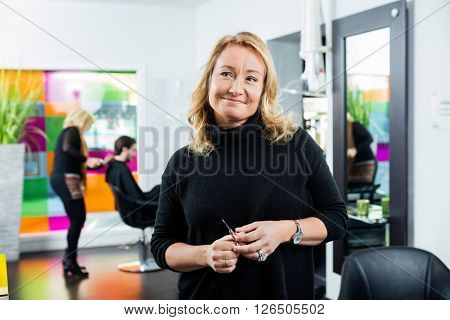 Thoughtful Female Hairstylist Holding Scissor
