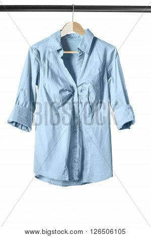 Blue cotton blouse on clothes rack isolated over white