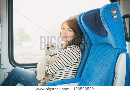 Dog traveling by train with his owner