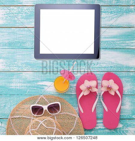 Blank empty tablet computer on beach. Trendy summer accessories on wooden background pool. Sunglasses, orange juice and flip-flops on beach. Tropical flower orchid. Flat mock up for design. Top view.