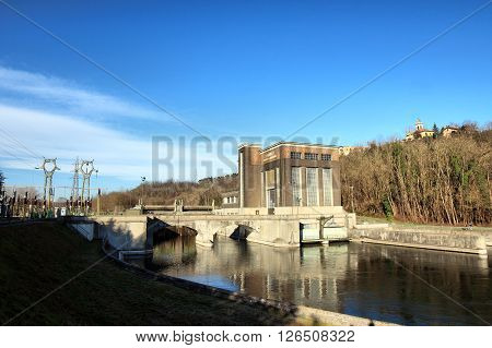 TORNAVENTO ITALY - FEBRUARY 21 2016: hydro-electric power plant and the old church at the top of the Hill