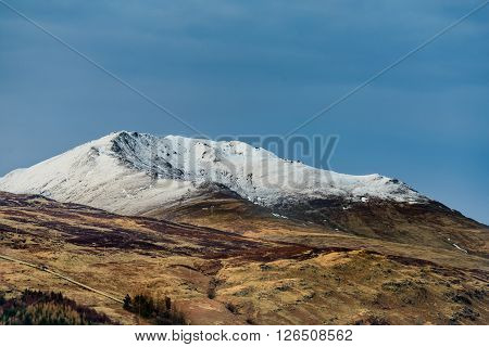 Snow capped Beinn Ghlas and Ben Lawers in late evening sunlight Killin Scotland
